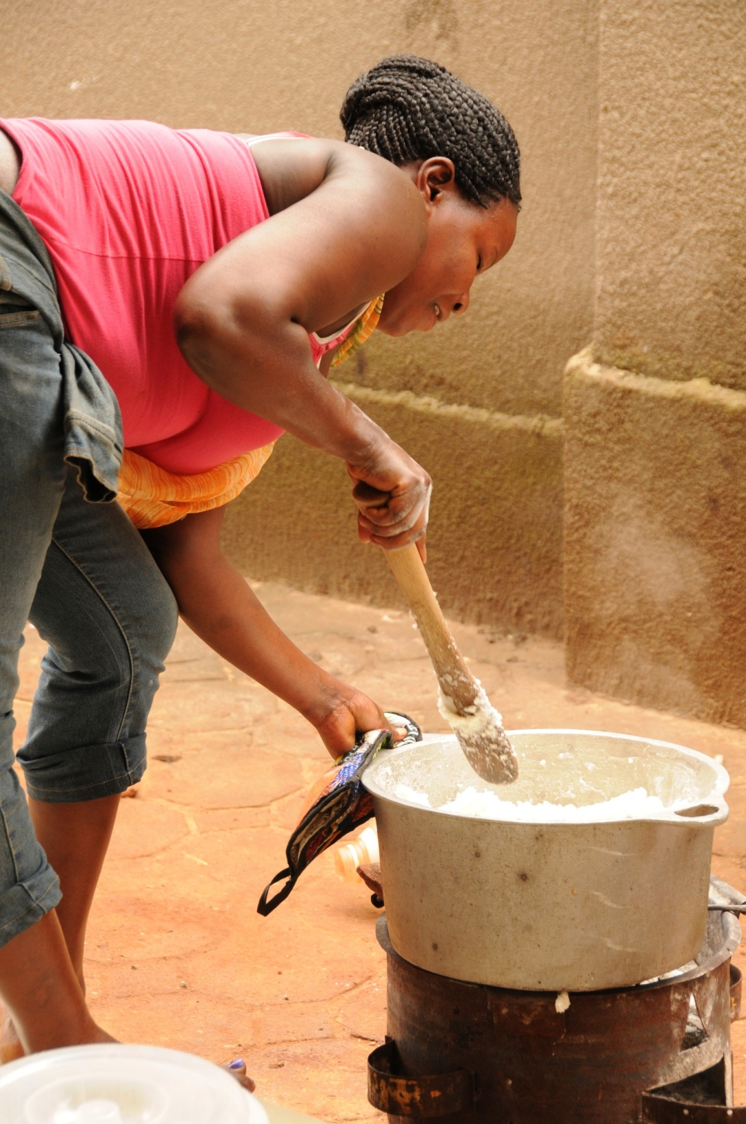 Judith is stirring the posho. It is so hard to do she works harder than the men building a wall.