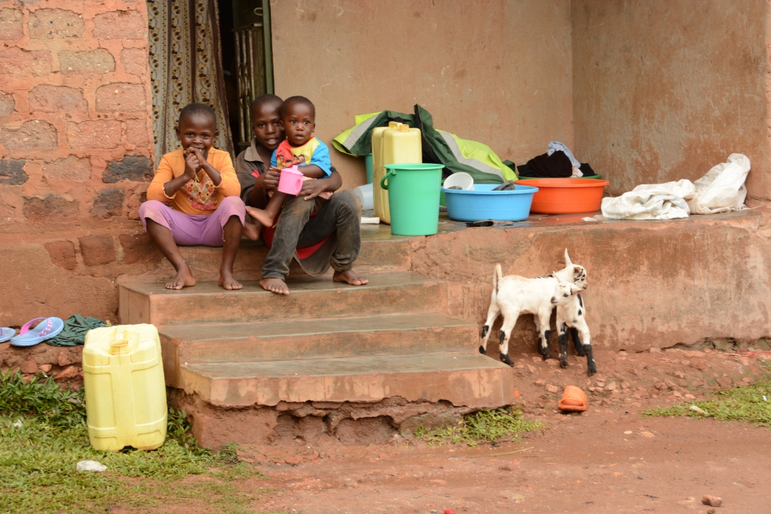 this is a typical sight in front of someones home. kids. laundry. jerricans. goats. chickens. smiles!