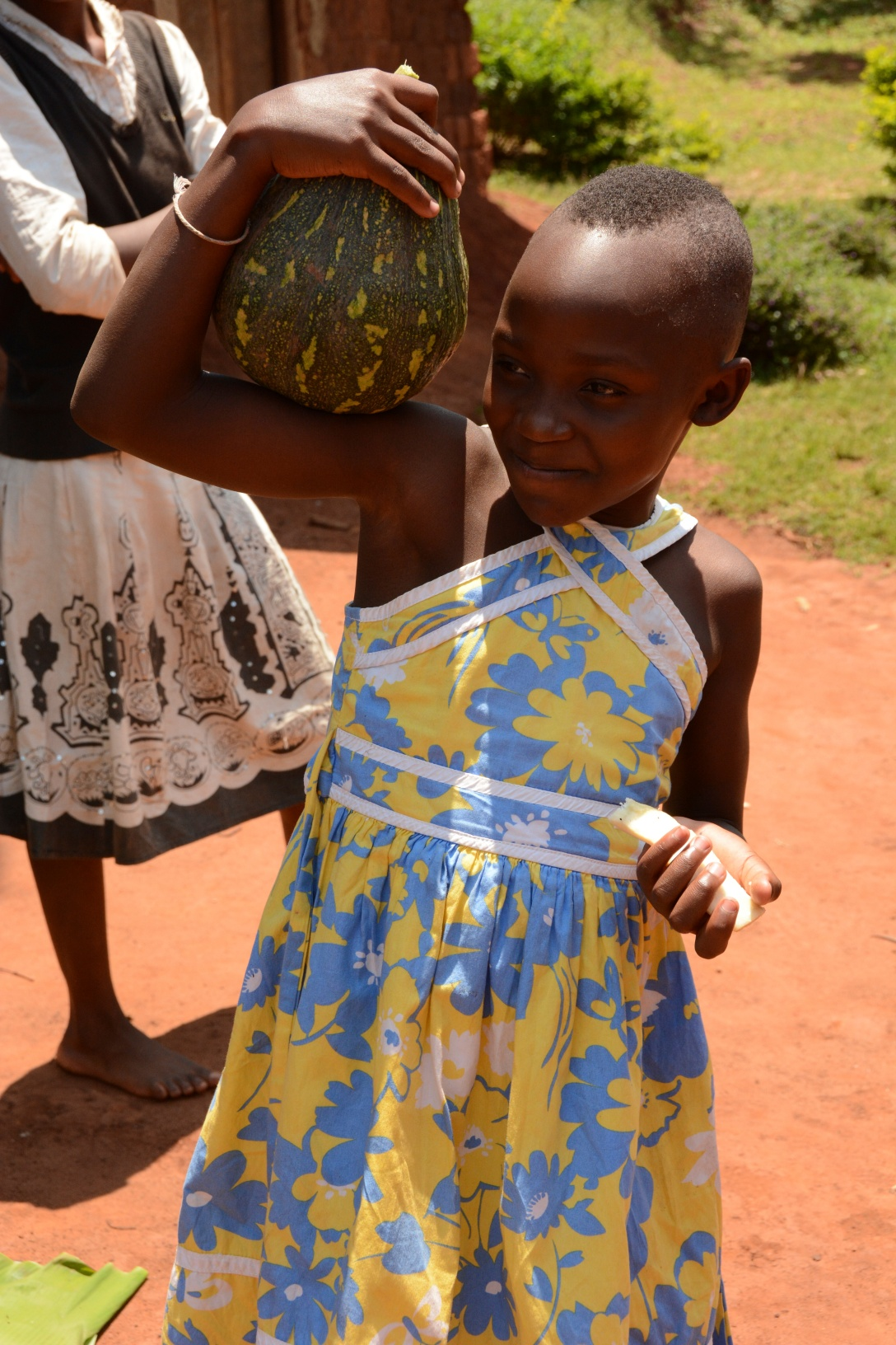 Victoria carrying a pumpkin...which is kira's favorite food in Uganda! Steamed fresh out of the garden is awesome.