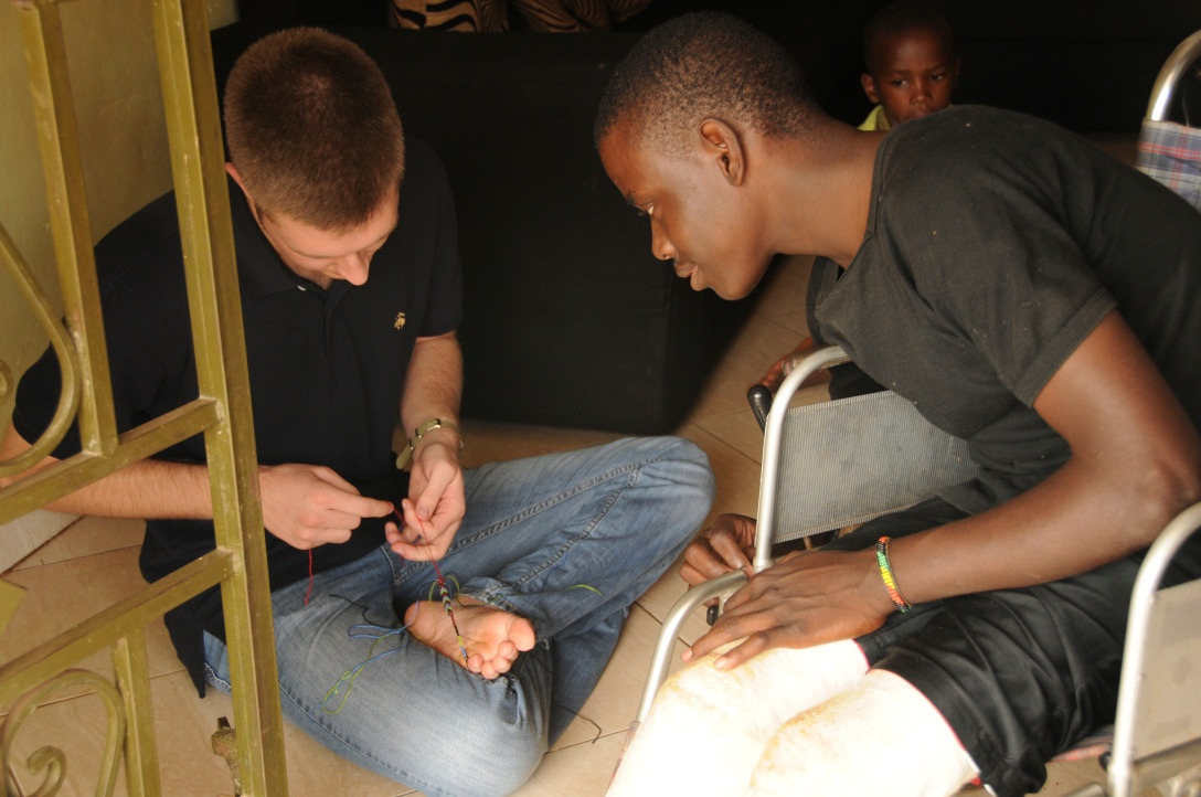 Fred and Christopher tying knots for a bracelet