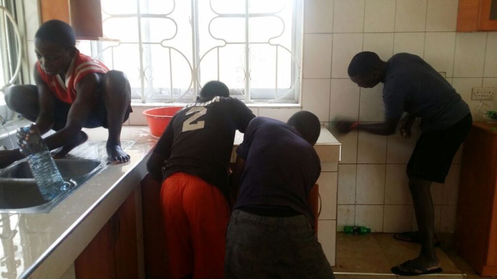cleaning up the new kitchen in the house Kirabo Seeds recently purchased for the organization.