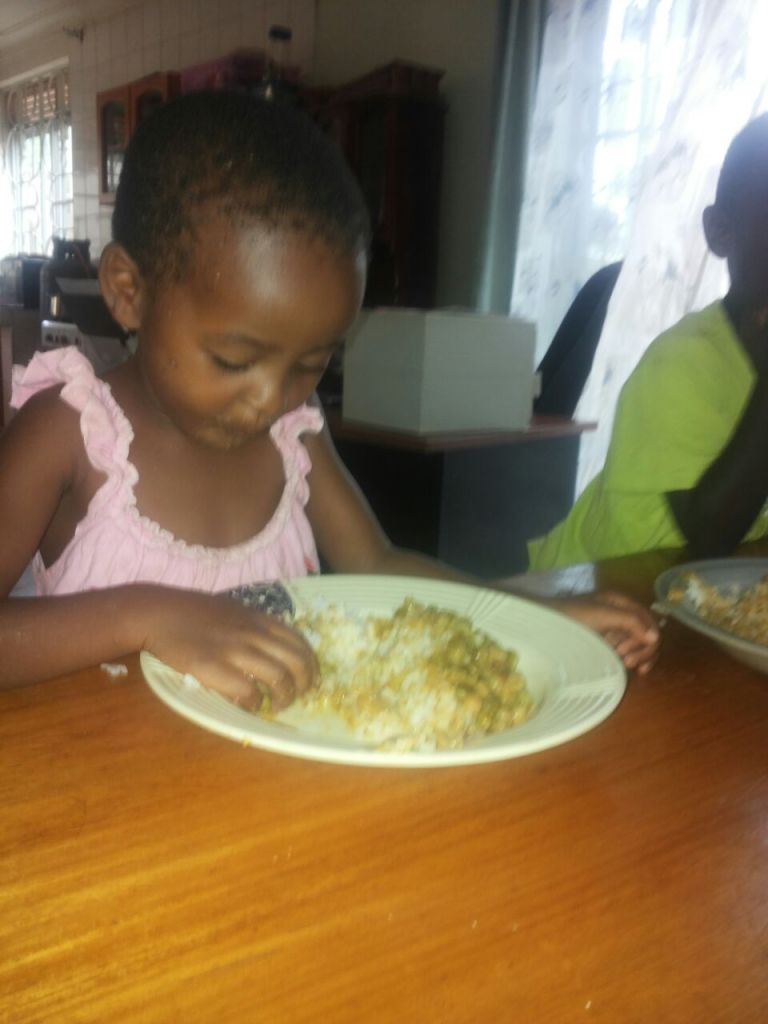 Justine enjoying her meal... don't be horrified... most people use their hands to eat in Uganda by choice.